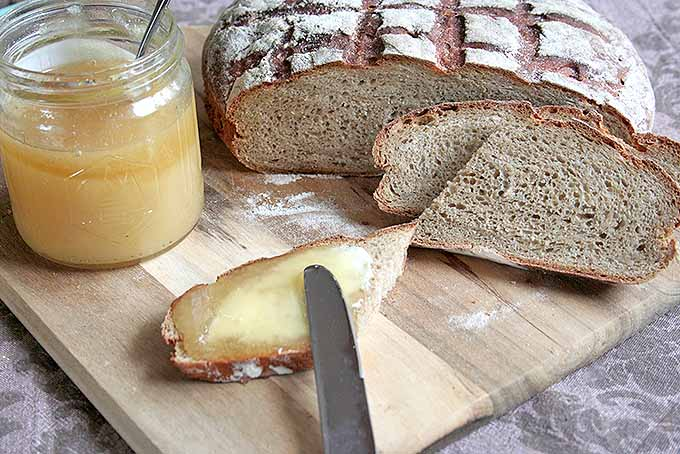 Spreading some homemade dark rye bread slices with honey for a tasty treat. | Foodal.com