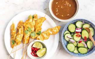 The perfect handheld dinner: spicy peanut chicken satay with a cucumber salad on the side. | Foodal.com
