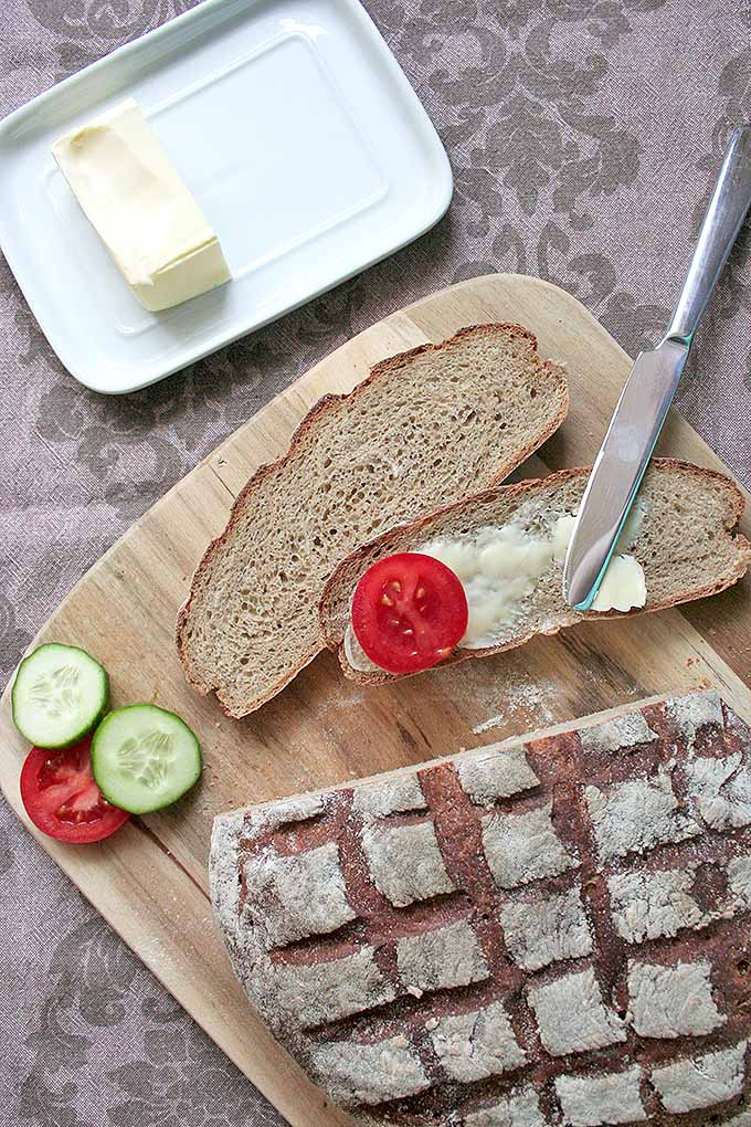 Homemade German dark rye bread is a malty bread that goes perfectly with a variety of toppings, like butter and fresh tomatoes and cucumbers. Make the recipe today: https://foodal.com/recipes/breads/dark-rye-bread-a-european-tradition/