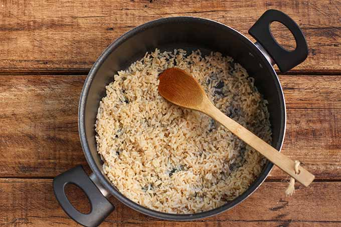Cooked brown rice is the grain base for our hearty vegetarian burrito bowl. | Foodal.com