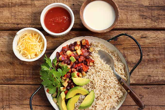 A big plate of our hearty veggie burrito bowl with avocados and other tasty accompaniments. | Foodal.com