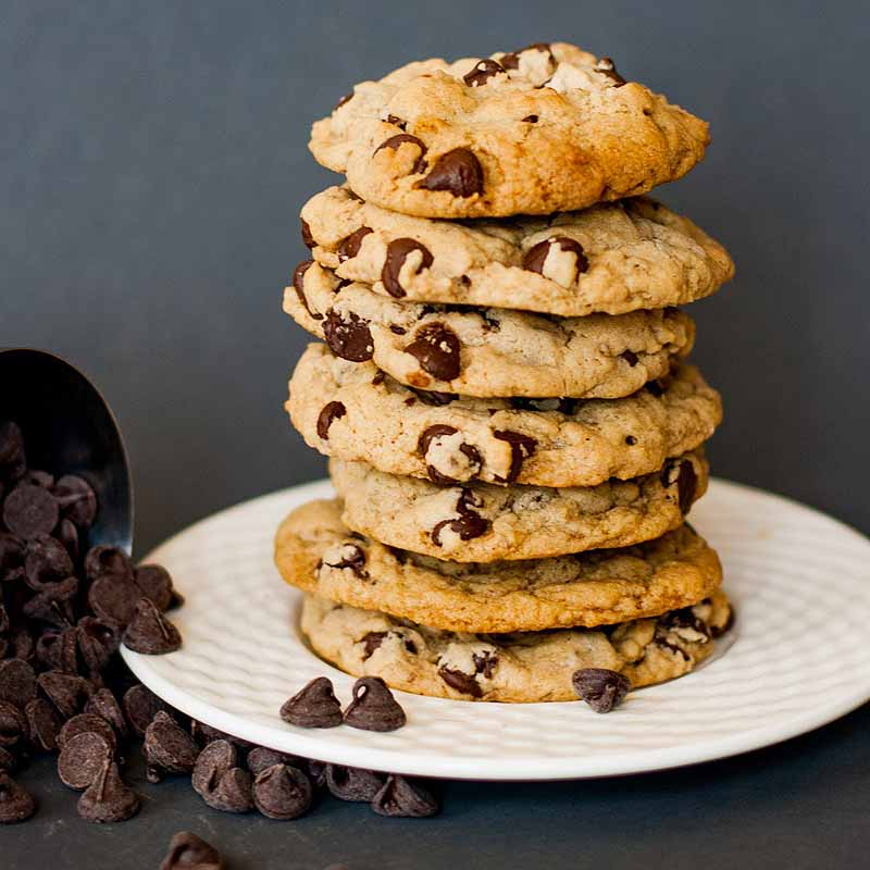 Side view of a stack of vegan cookies on a white ceramic plate on a dark gray background. A pile of loose chocolate chips is to the left of the plate.