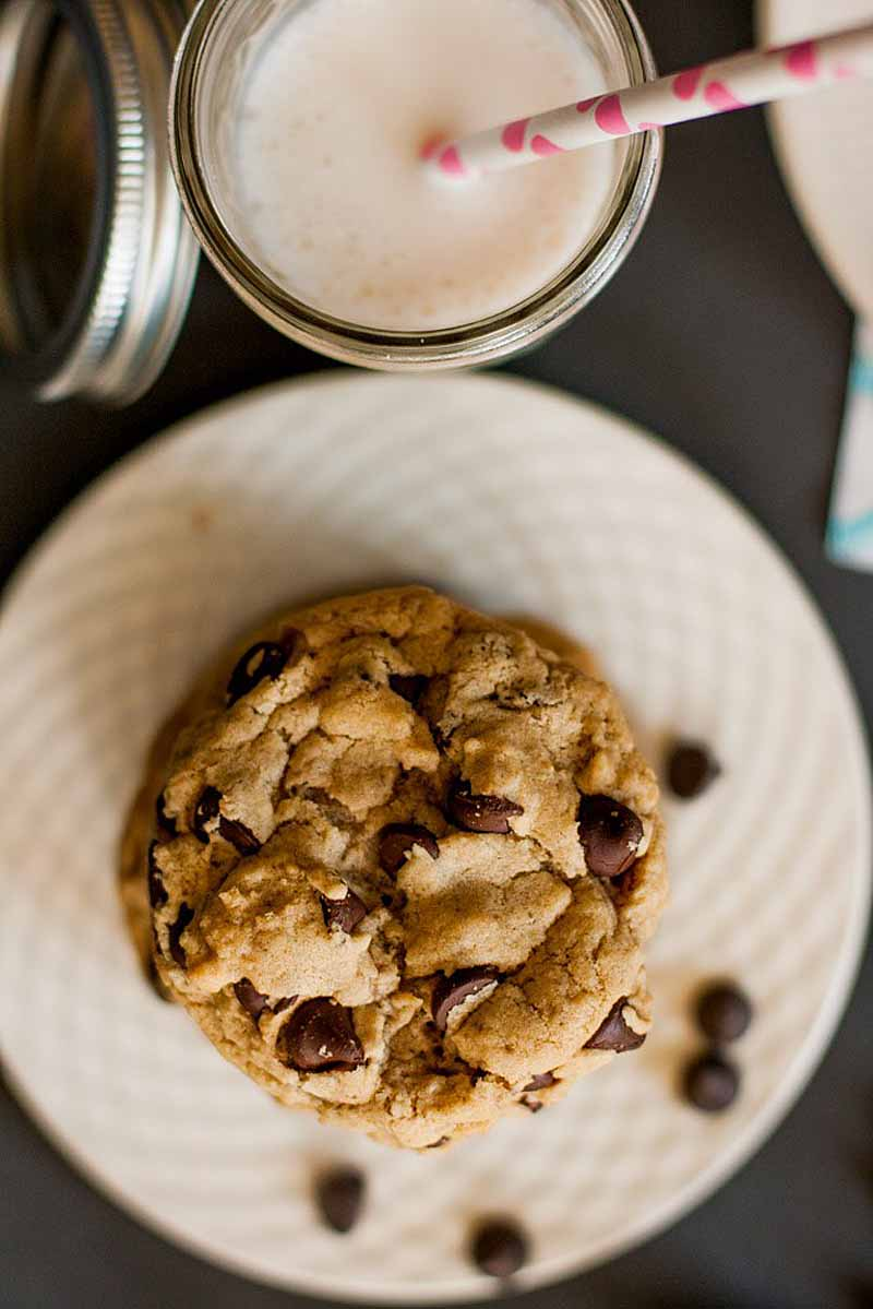 Top down view of a stack of vegan chocolate chip cookies on a white porcelain platter. A glass of cold almond milk is at the top of the frame. Glass and plate is sitting on a dark gray back ground.