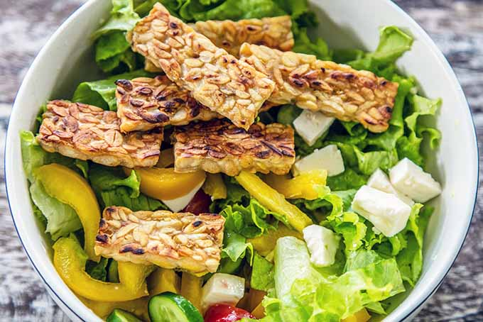 Enjoy a salad topped with tempeh for a delicious gut-healthy ingredient. | Foodal.com
