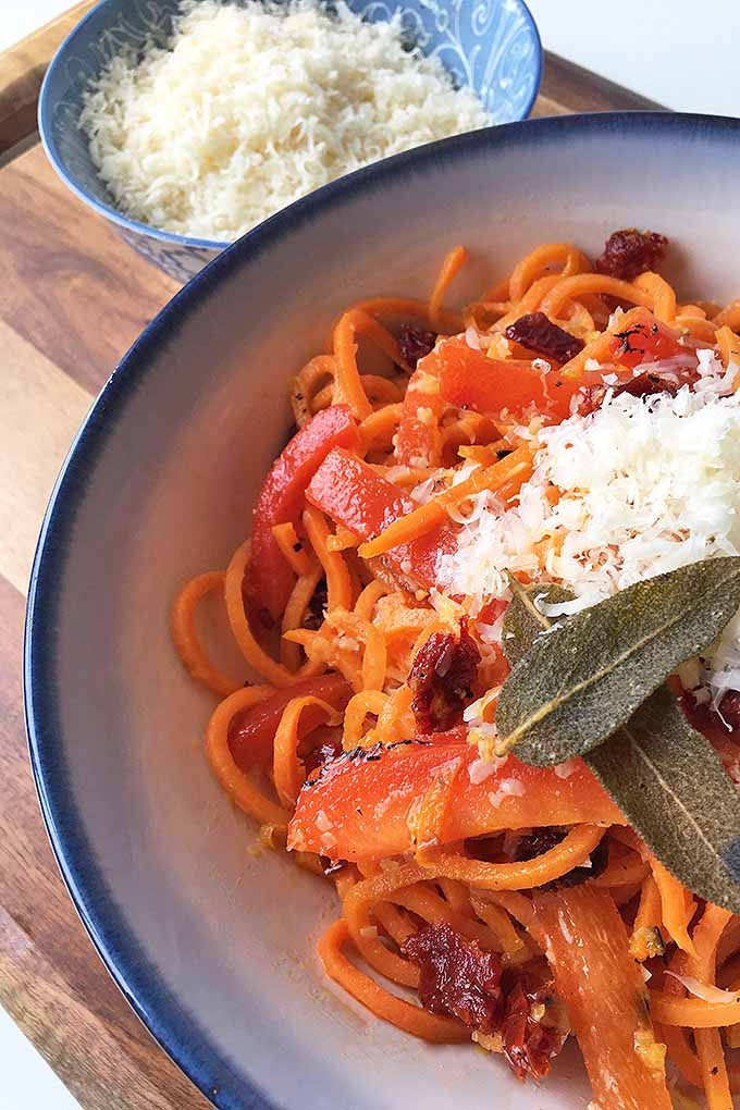 Vertical image of sweet potato noodles with peppers, sun dried tomatoes, sage leaves, and cheese on a blue-lined white plate, and a bowl of grated cheese on the side on a wooden cutting board.