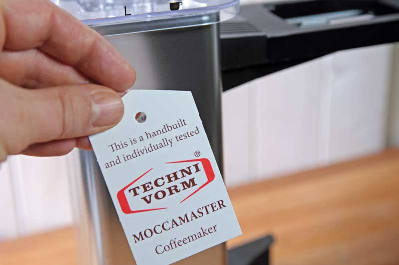 A human hand holding a tag certifying that the Technivorm Moccamaster was hand crafted and tested in the Netherlands.