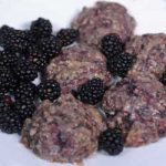 Close up of a batch of freshly baked blackberry scones with fresh fruit.