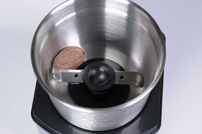 A whole nutmeg being ground by the Cuisinart DCG-12BC.