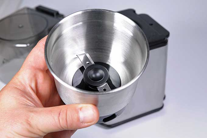 Human hand holding the removable cup from the Cuisinart DCG-12BC.
