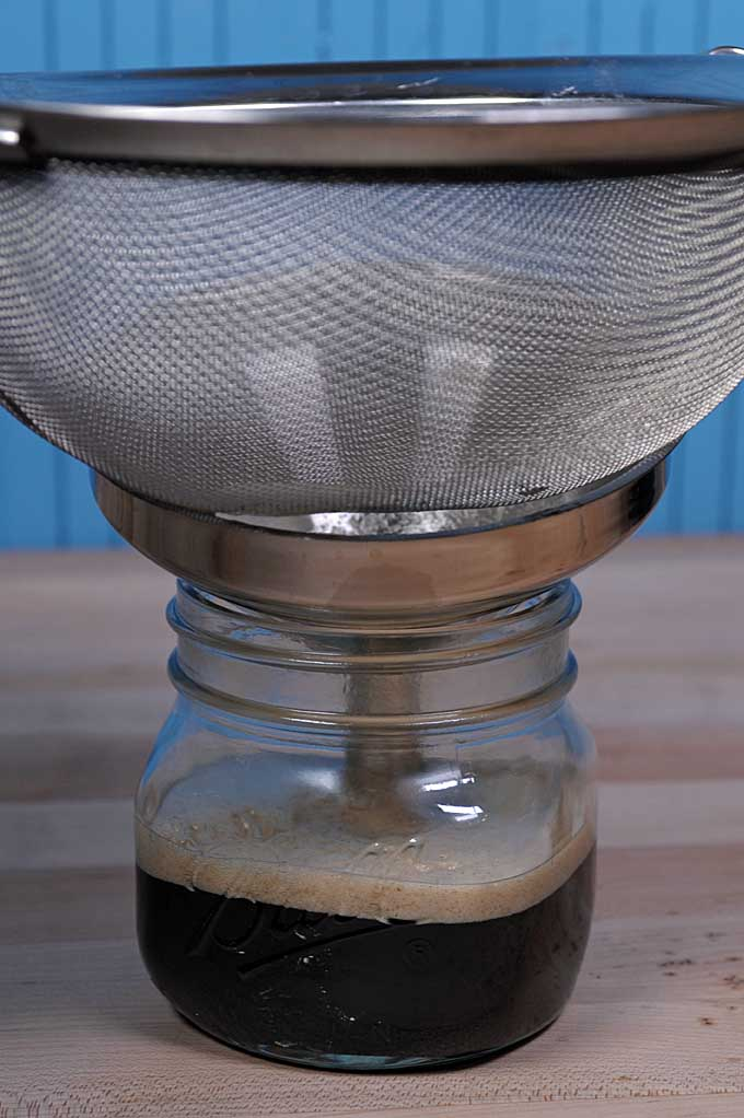 Brown butter being filtered by a mesh strainer and then funneled into a canning jar | Foodal