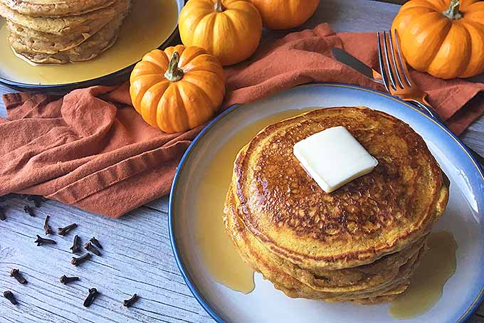 Oblique view of a stack of pumpkin spice pancakes with butter and maple syrup on a rustic white wooden surface.