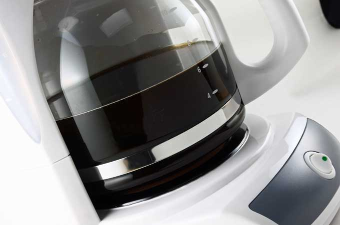 A closeup of a glass carafe attached to an automatic drip coffee maker.