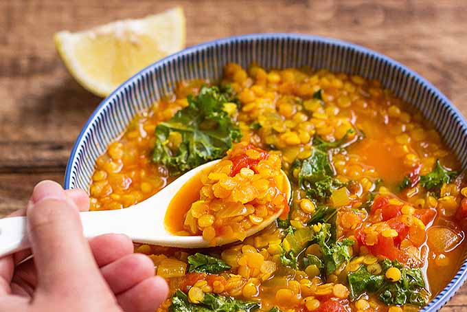 A white ceramic spoon is being used to scoop out a mouthful of turmeric and kale lentil soup from its serving bowl.