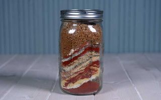 A mason jar filled with layered spices for a mixture used to make a superb all-purpose chicken dry rub. | Foodal