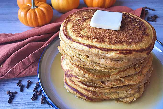 Oblique view of a stack of pumpkin spice pancakes on a plate with butter and maple syrup applied.
