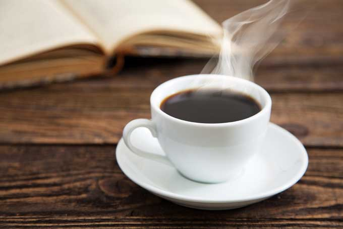 A white cup of coffee sits on a rustic wooden desk with a hard copy book open in the background.