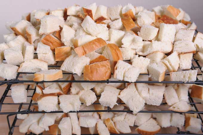 Bread chunks on a black drying rack | Foodal