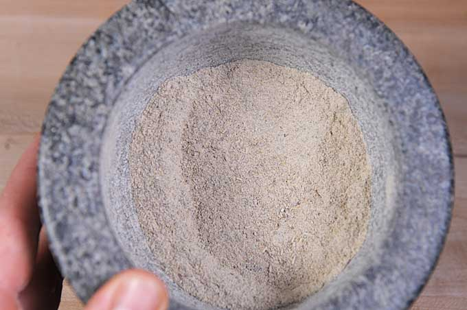 Top view of a mortar and pestle with the dry rub ingredients being ground into a medium coarse powder | Foodal