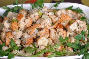 Side shot of homemade bread stuffing in a white, ceramic serving dish | Foodal