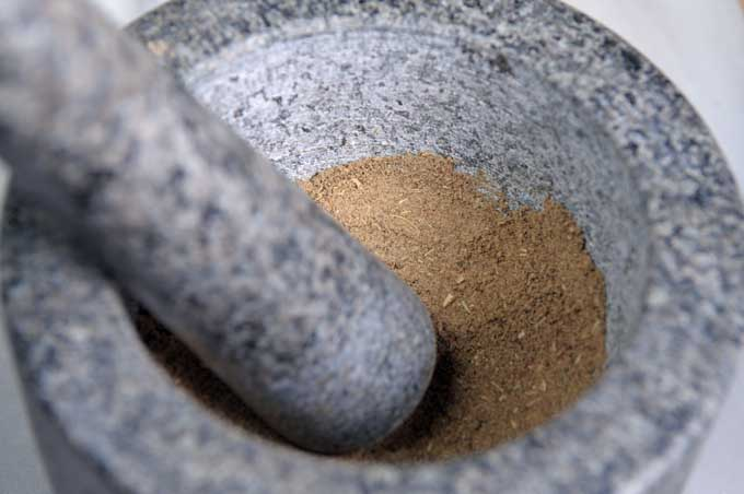 A close up of a mortar and pestle grinding up poultry seasoning | Foodal