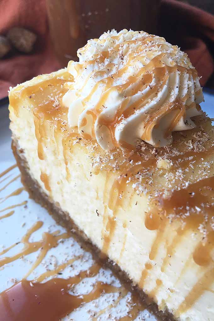 Served with whipped cream and caramel sauce, our decadent and boozy eggnog cheesecake will secure your spot on Santa's naughty list! Get the recipe now: https://foodal.com/recipes/desserts/spiced-eggnog-cheesecake/