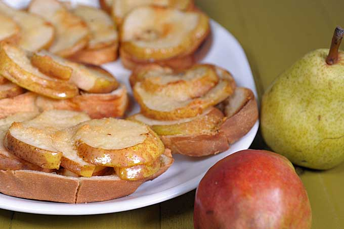 Oblique view of a six maple pear crostini breads on a white ceramic plate on a green wooden background. Fresh Bartlett and red pears sit to the right   Foodal
