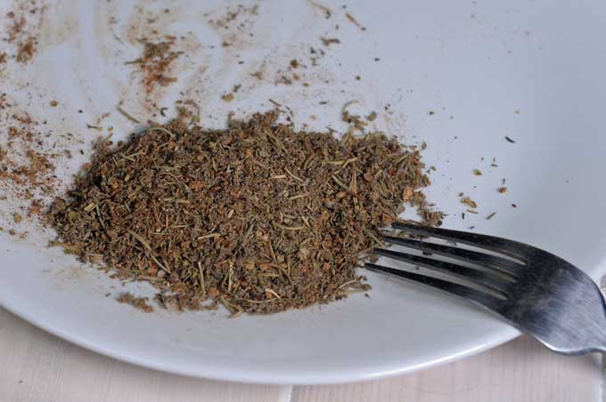 A fork mix herbs and spices together on a white ceramic plate | Foodal