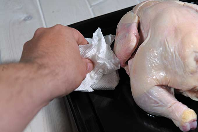 "A human hand soaks up excess chicken ""juice"" with a paper towel 