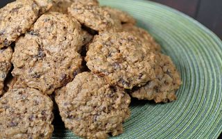 A pile of oatmeal chocolate chip cookies on a green circular place mat | Foodal