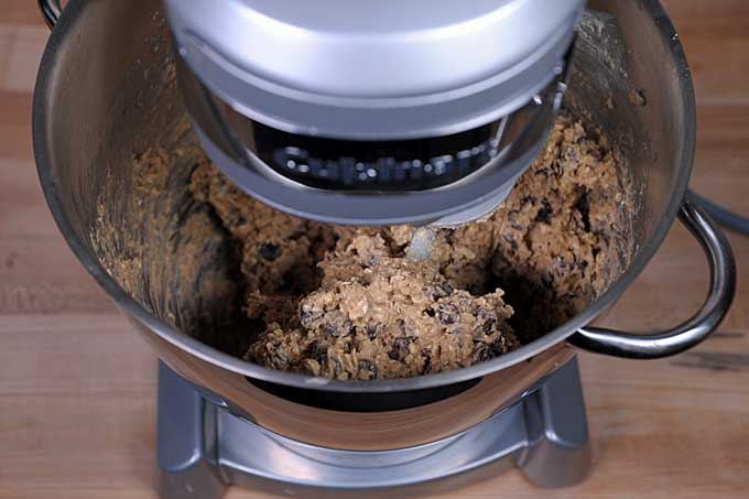 A close up of a stand mixer bowl with the dough for oatmeal chocolate chip cookies inside of the bowl | Foodal
