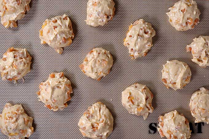 Top view of raw peach cookie dough balls on Silpat baking mat | Foodal