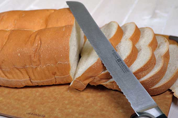 Oblique view of partially sliced loaf of Italian bread and a serrated bread knife | Foodal