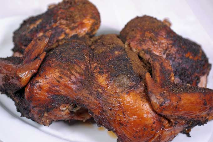 Close up of the breast area of a smoked and dry brined and rubbed turkey on a white ceramic plate and white wooden background   Foodal