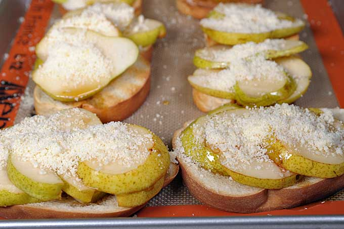 Close up shot of crostini on a Silpat silicone baking mat on a cookie sheet | Foodal