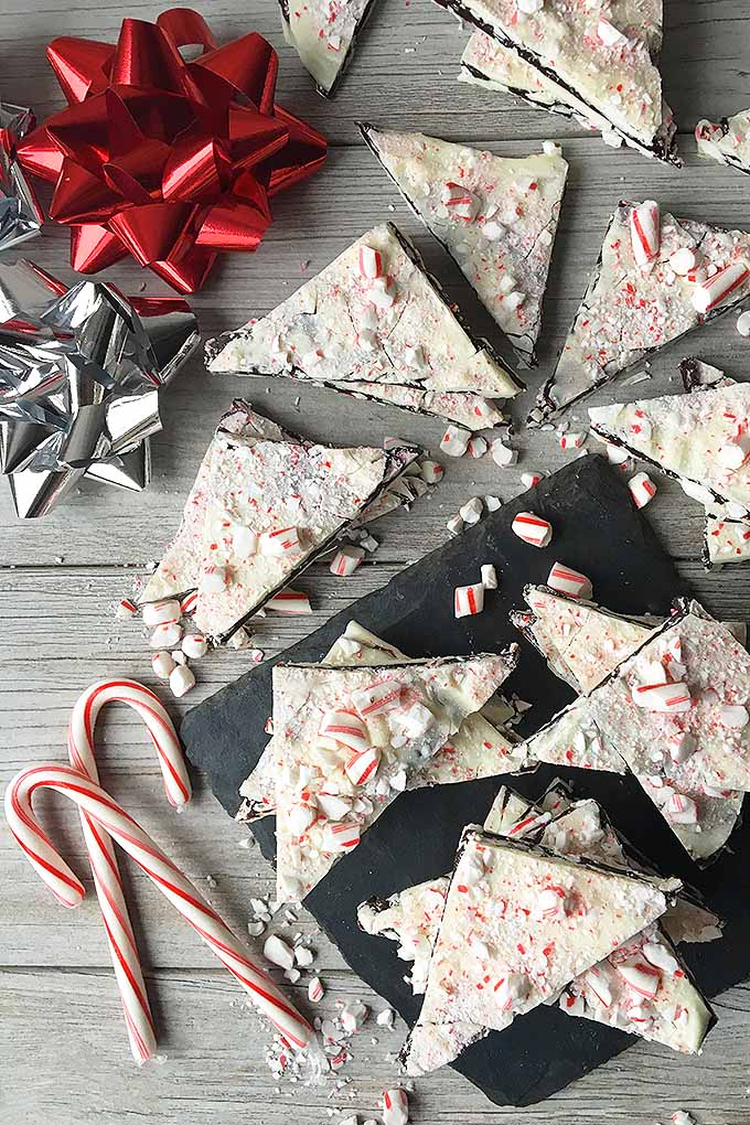 Top down view of Christmas peppermint bark candy made of layers of chocolate and white chocolate ganache and topped with crushed peppermints. Triangular pieces of the bark lay scattered on a gray weathered table top. Bows made of red and silver ribbons are mixed in along with with two candy canes.