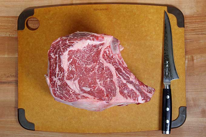 Top down view of a bone-in prime rib with a boning knife on a cutting board | Foodal