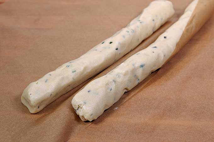 Two logs of rosemary butter cookie dough on parchment paper | Foodal
