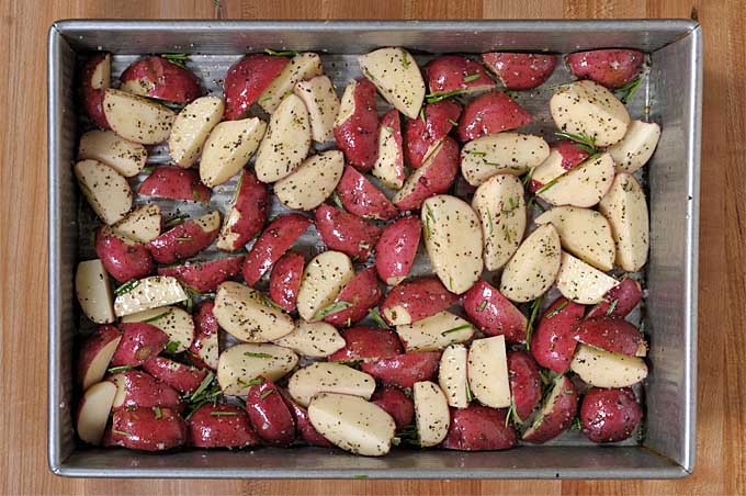 A metal cake pan full of raw rosemary red potatoes | Foodal