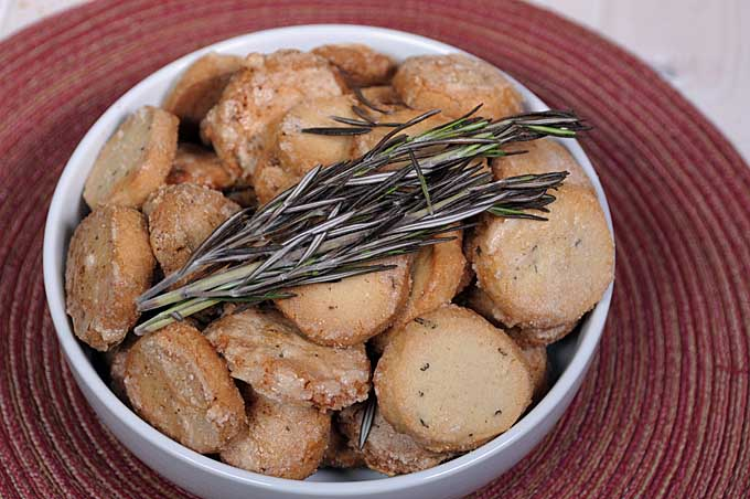 A white ceramic bowl with rosemary butter cookies with fresh rosemary leaves on top | Foodal