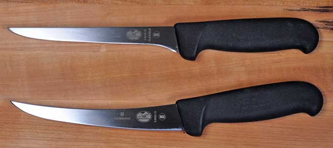 A pair of Victorinox Fibrox Pro Boning Knives: one with a curved blade and one with a straight blade | Foodal