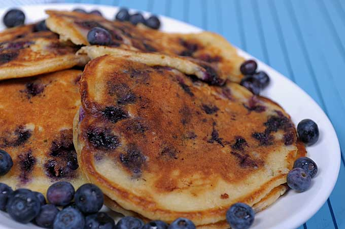 Close up of a platter full of Buttermilk Blueberry pancakes on medium blue background | Foodal