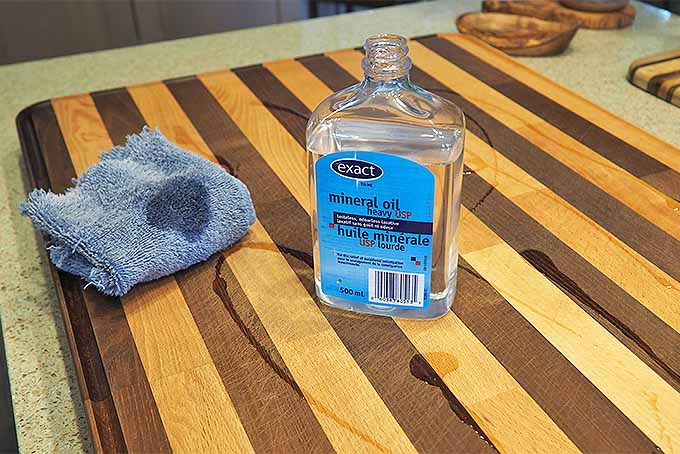 Mineral oil being applied to a wooden cutting board | Foodal