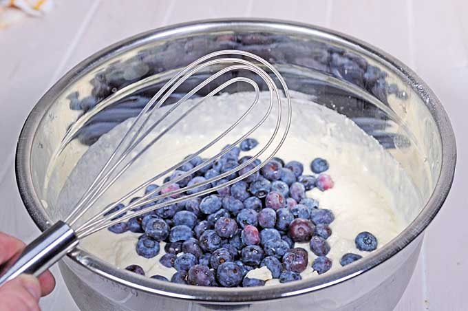 The blueberries are being folded into the pancake batter using an OXO flat whisk | Foodal