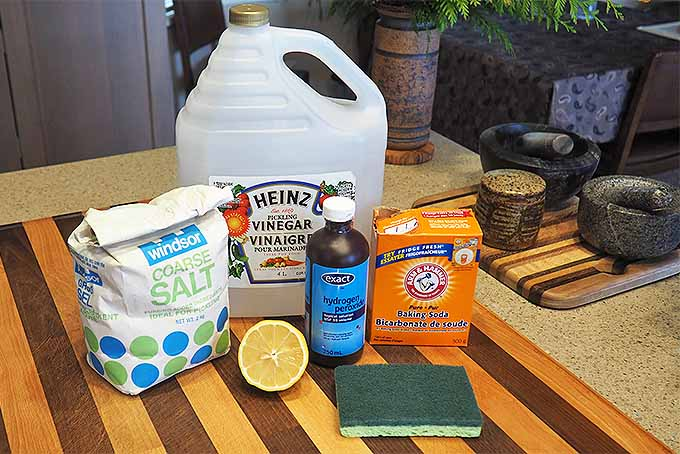 An array of natural cleaning products such as vinegar, salt, lemon, baking soda, and hydrogen peroxide sit on a wooden cutting board | Foodal