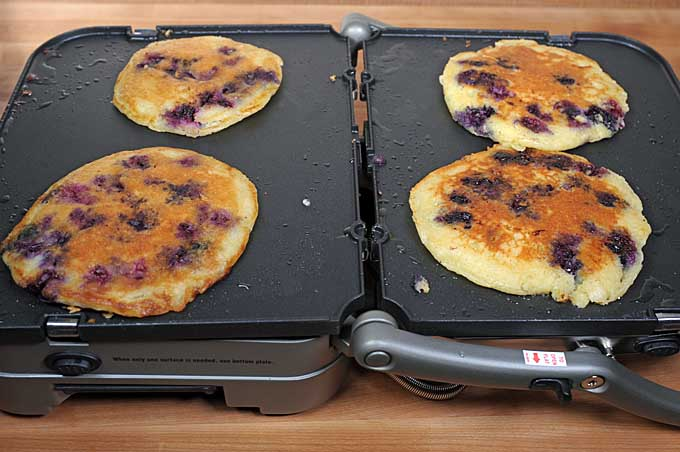 The blueberry pancakes have been flipped and the uncooked side is being browned on the Cuisinart GR-4N 5-in-1 Griddler | Foodal