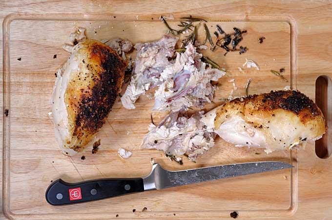 Top down view of lemon roasted chicken breast sliced apart on a cutting board by a boning knife | Foodal