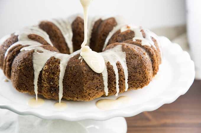 Square image of a brown banana bundt cake with white maple glaze being drizzled onto the top of the cake from above, on a white cake stand atop a brown wooden table.