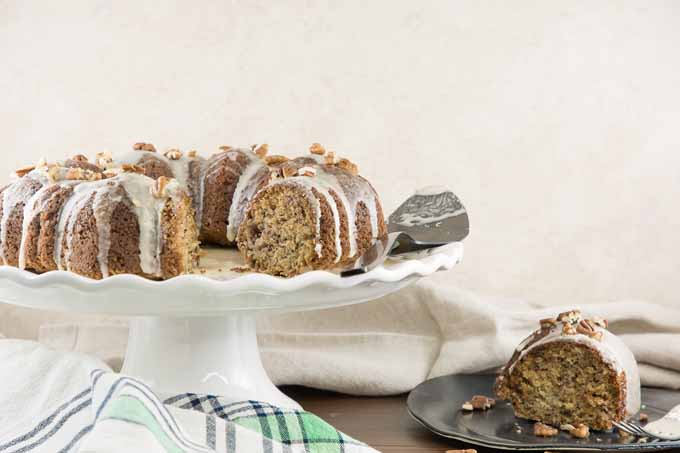 A banana bundt cake on a white cake stand with maple glaze and sprinkled with pecans, sliced so the crumb is visible, with a slice of cake on a gray plate to the right, and a folded white and green cloth to the left, on a brown wooden table with a beige background.
