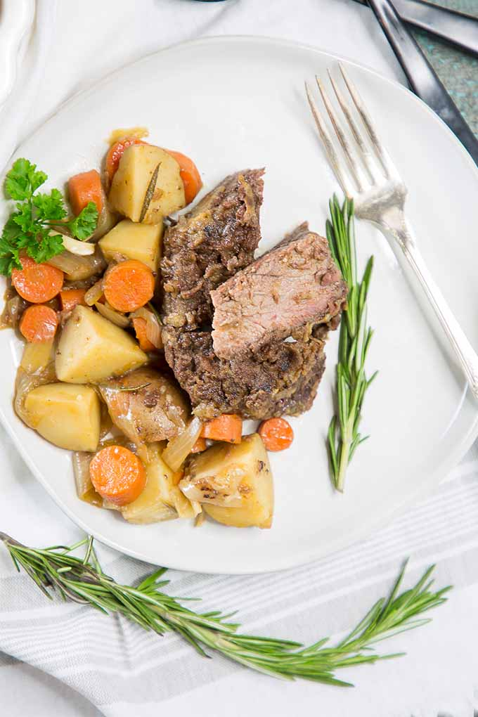Top down view of a pot roast with carrots and potatoes on a white ceramic plate surrounded by fresh thyme leaves.