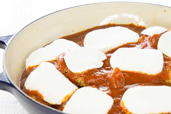 Close up view of fresh mozzarella cheese added to a topping of marina sauce on top of bread chicken breasts to make chicken Parmesan | Foodal